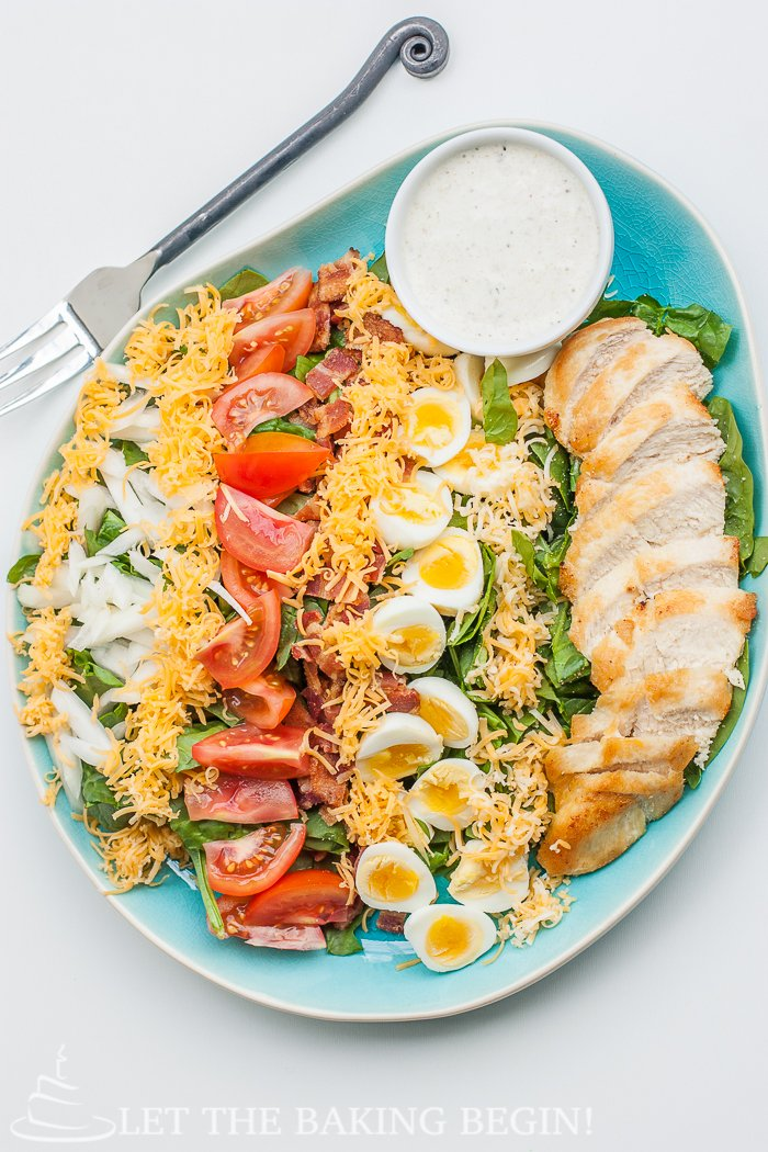 Top view of cobb salad in a decorative bowl topped with ingredients and fresh greens.
