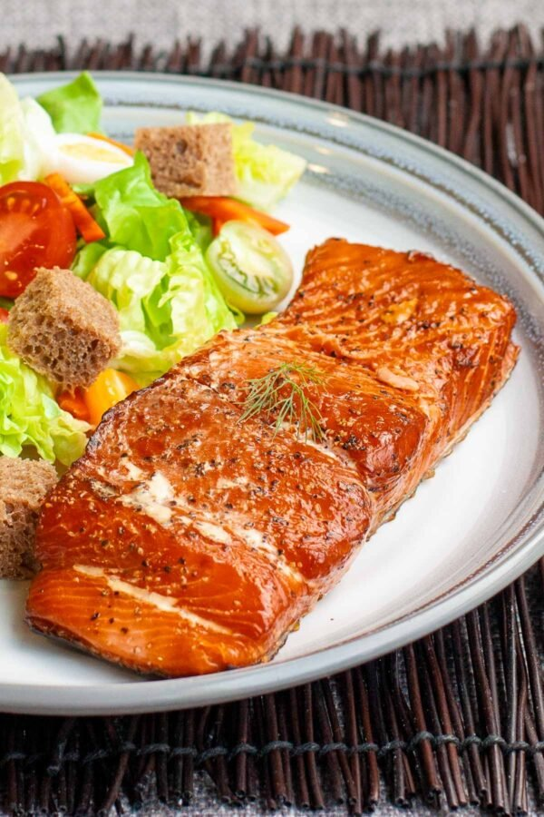 Seasoned smoked salmon fillet on a plate with a salad.