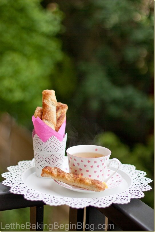 Chocolate filled croissants on a white plate with a cup of tea.
