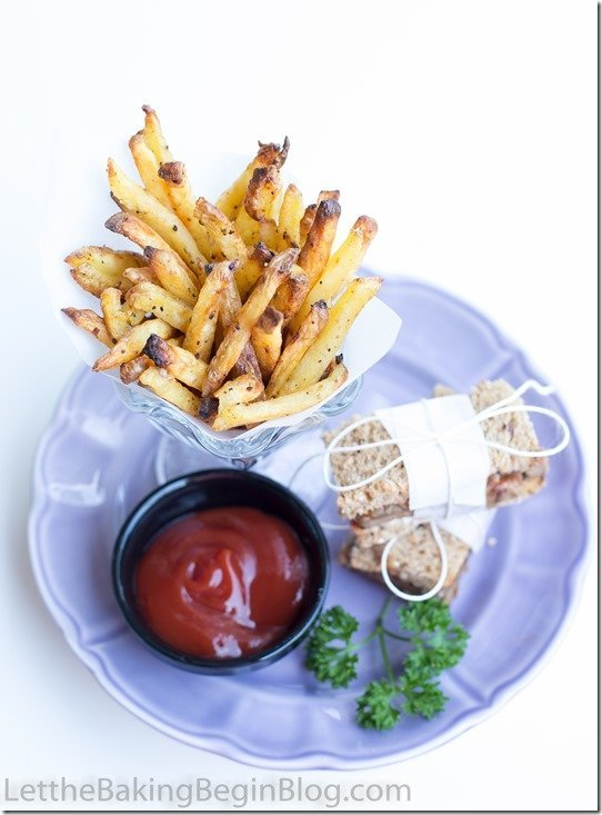 French fries topped with ground black pepper with a ramekin of ketchup on a blue plate.
