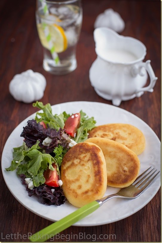 Potato pancakes on a white dinner plate with a side salad.