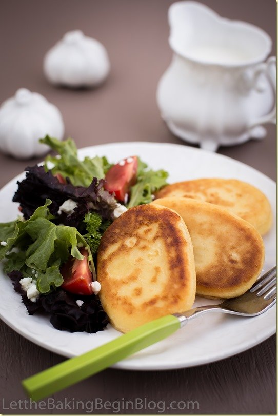 Crispy mashed potato pancakes on a white dinner plate with a salad and fork