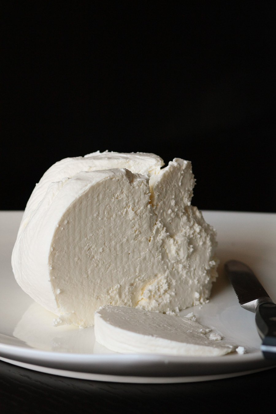 Homemade Farmer's cheese recipe on a plate with a butter knife.