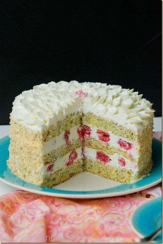 Lemon cake with poppy seeds and chantilly cream on a cake platter with fresh raspberries.