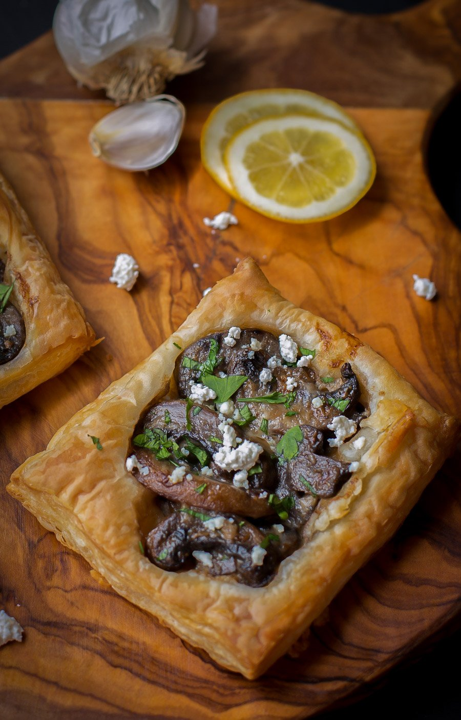 Goat cheese tart topped with goat cheese and fresh greens on a cutting board with goat cheese, lemons, and garlic.