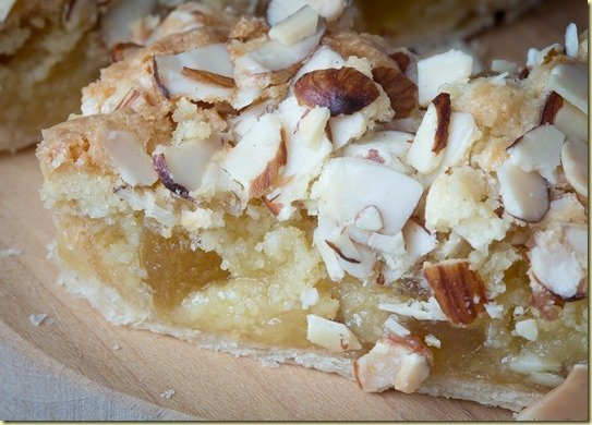 Almond & pineapple tart topped with almonds on a wooden cutting board.