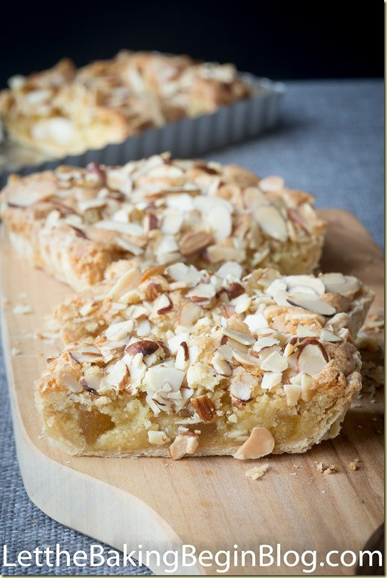 Puff pastry tart topped with sliced almonds on a cutting board.