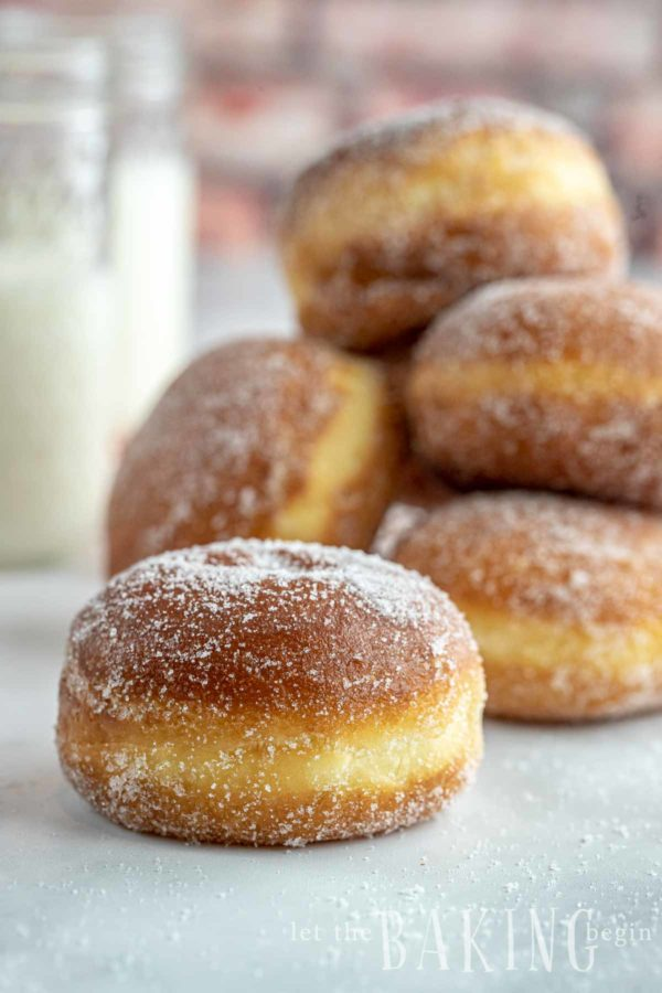 Homemade donut dredged in sugar in the foreground and a stack of donuts in the background.