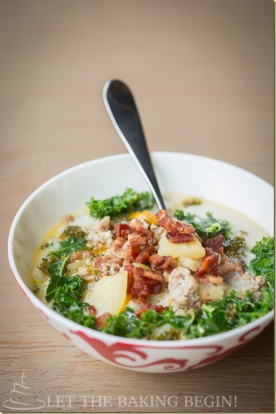 Hearty zuppa Toscana soup in a bowl with a metal spoon.