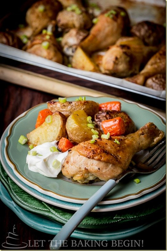 One pan meal made of baked chicken and potatoes on a baking sheet topped with fresh chopped greens.
