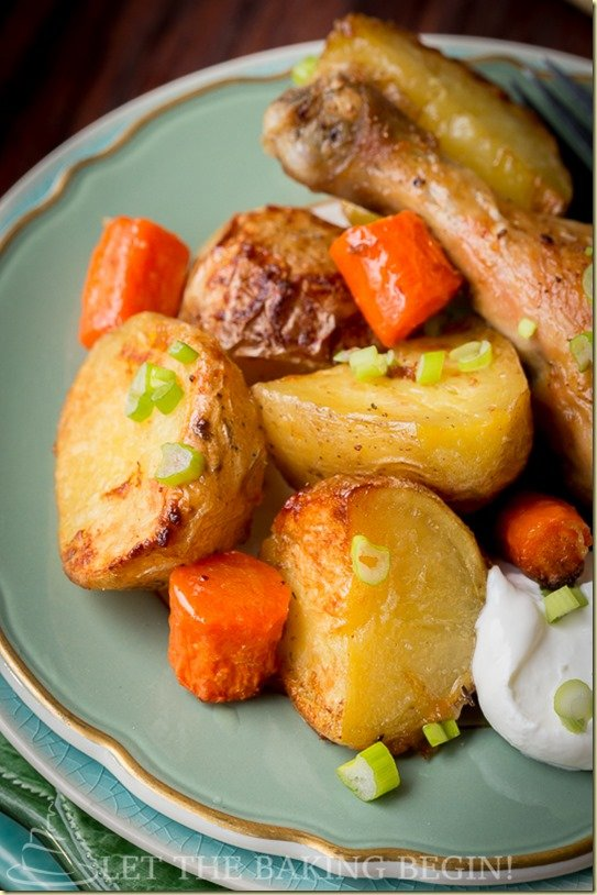 Baked chicken drumsticks and potatoes on a plate with carrots and greens.