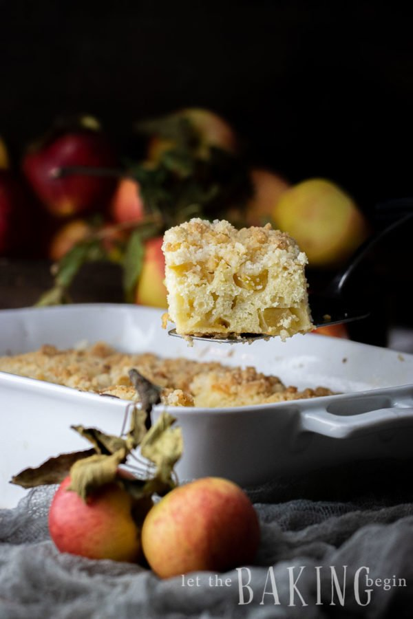 Apple coffee cake slice lifted up from the baking dish.