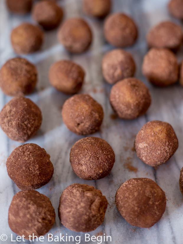 Chocolate Rum Balls coated in cocoa spread on a marble slab.