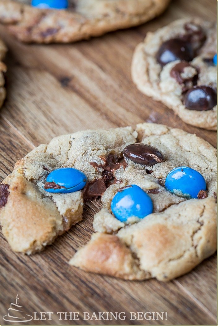 A chocolate cookie ripped into pieces with almond joy chocolate candy.
