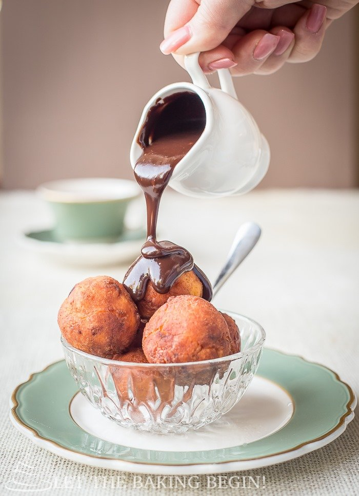 Donuts in a glass bowl on a green and white decorative plate being poured with a chocolate ganache.