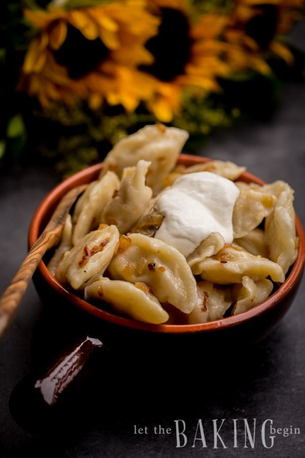 Perogies in an orange decorative bowl with a wooden spoon topped with a dollop of sour cream.