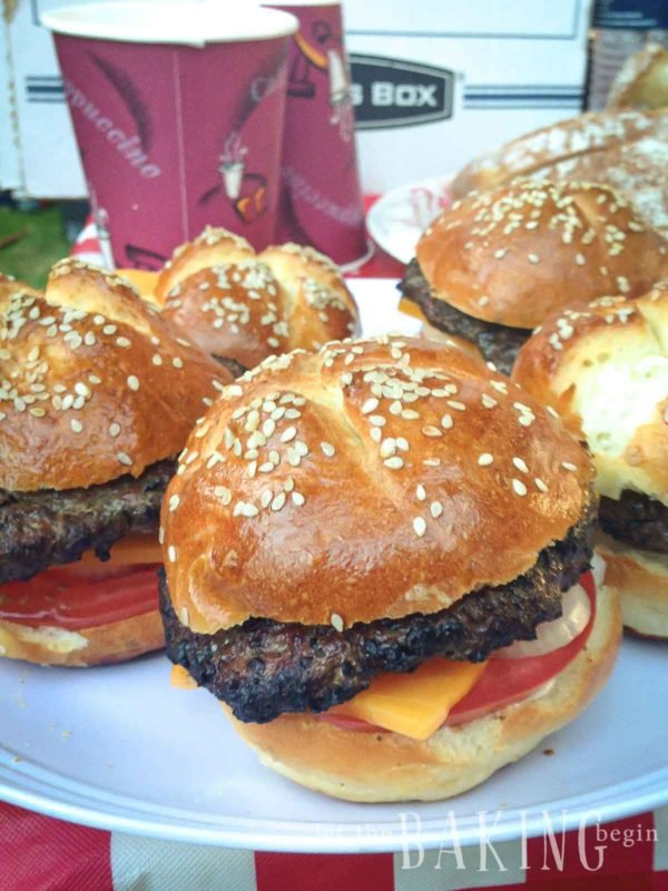 Cooked burgers on buns on a white plate.