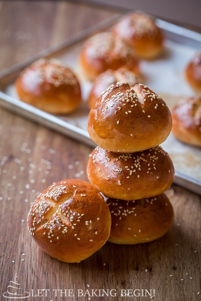 Four buns topped with sesame seeds laid out on a wooden table.