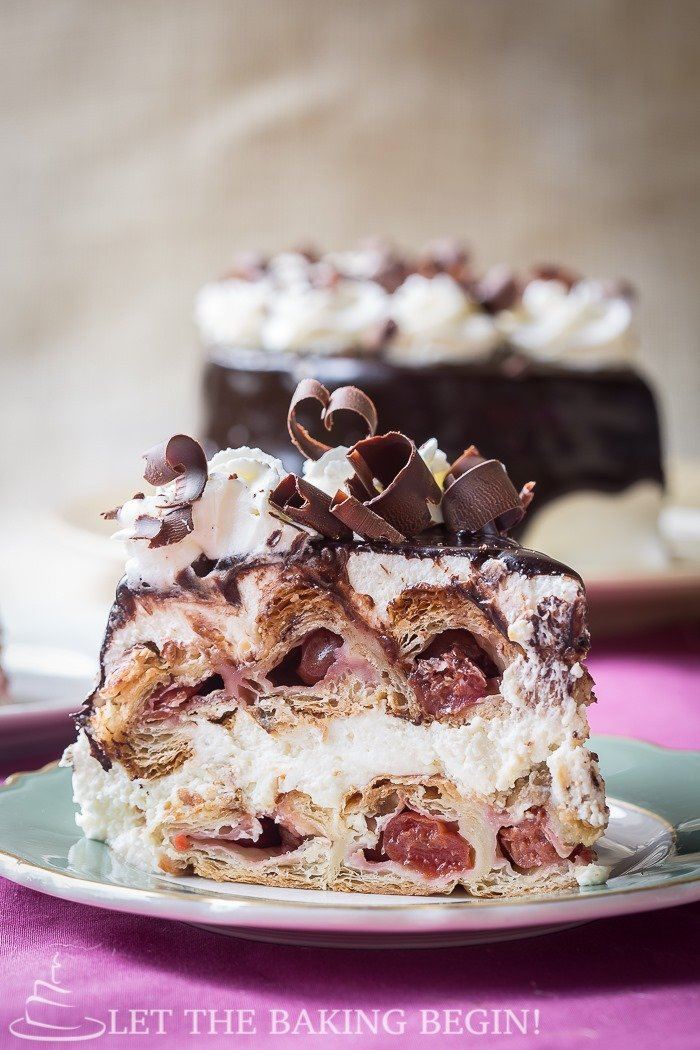 A slice of honeycomb cake made with puff pastry sheets filled with cherries and sour cream frosting topped with chocolate shavings.