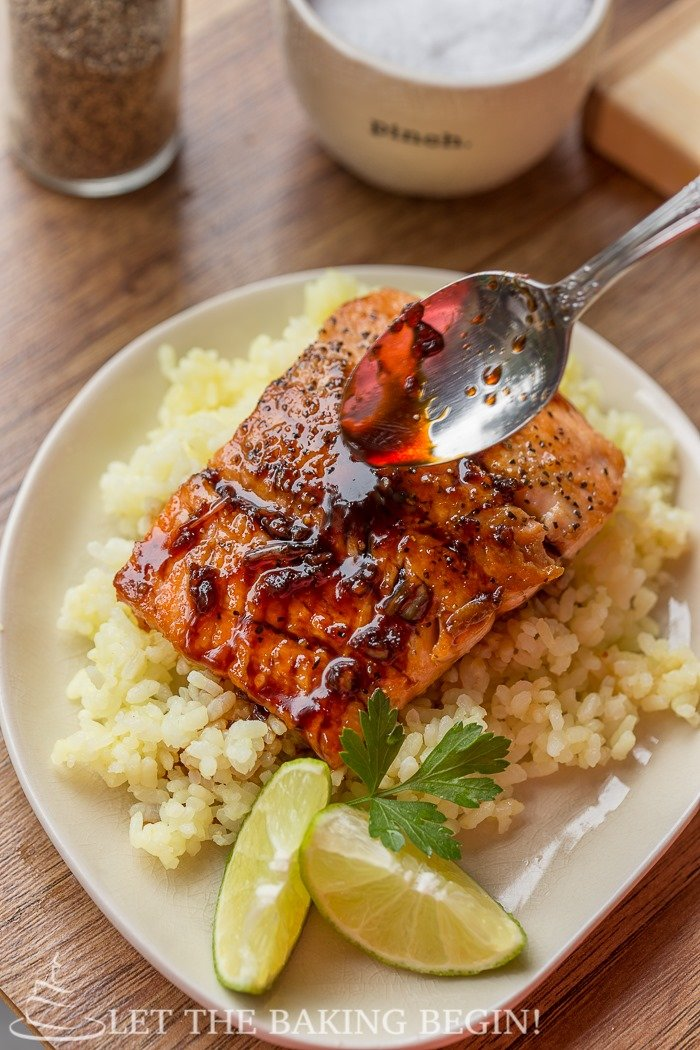 Garlic Ginger Glazed Salmon in a bowl with rice and limes with a spoon of the garlic ginger glaze drizzled with a spoon.