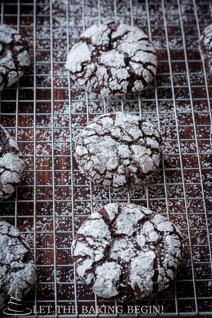 Cookies on a drying rack topped with powdered sugar.