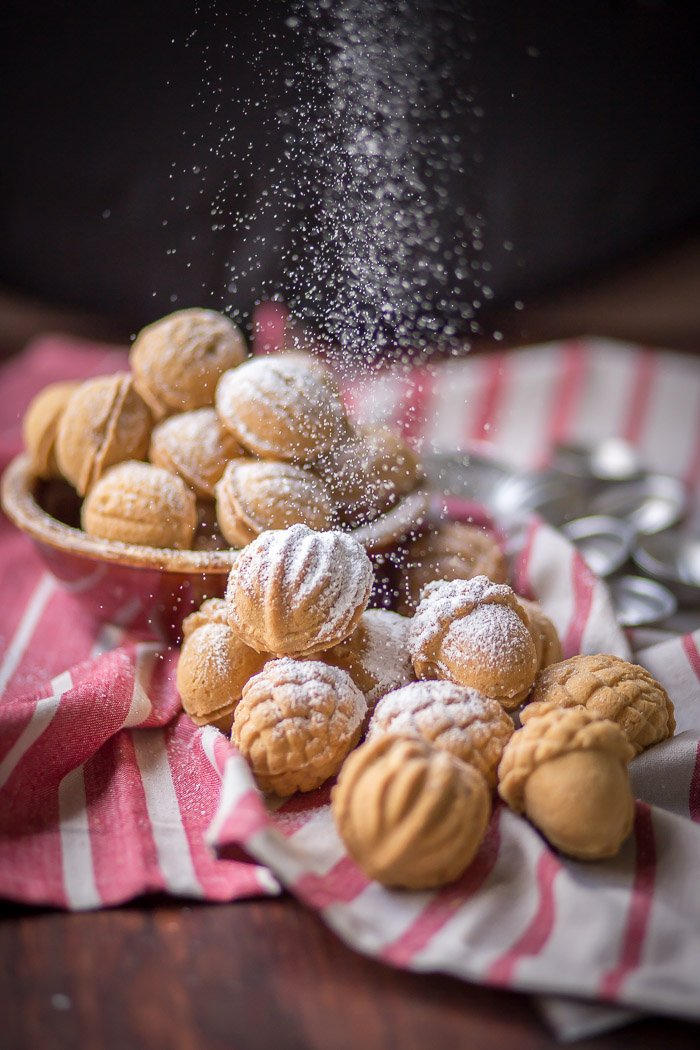Walnut shaped cooked in a bowl and on towel topped with powdered sugar.
