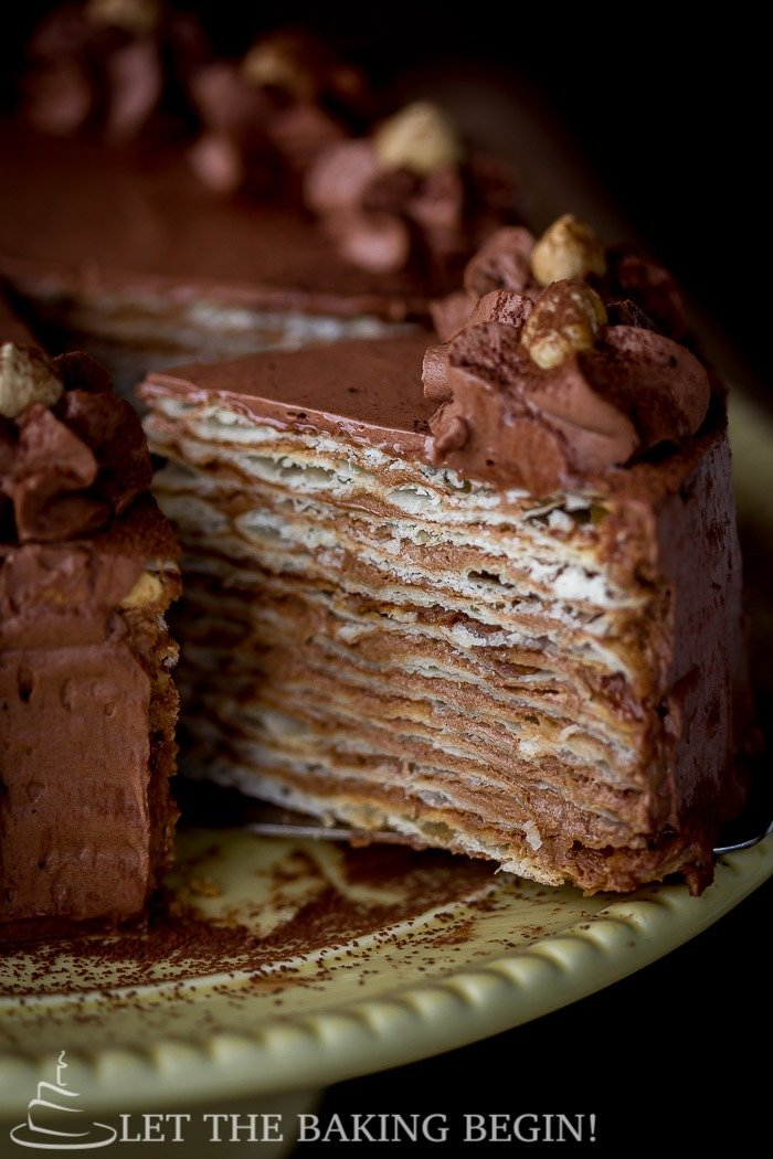 Mikado layer cake on a cake platter with a slice of cake.