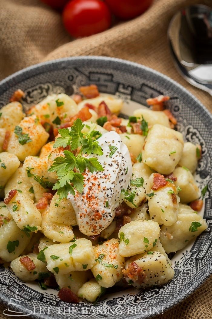 Potato Gnocchi recipe made with Bacon & Caramelized Onion in a bowl with a dollop of sour cream on top.