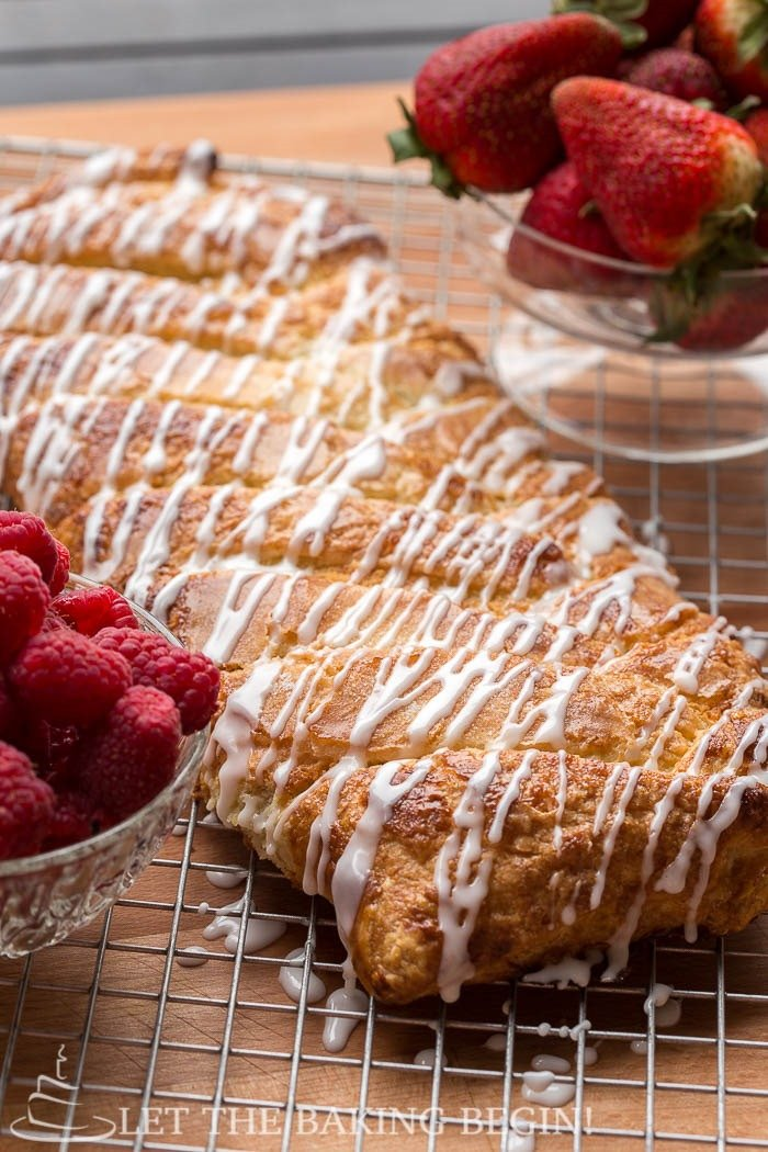 Puff pastry braid topped with a powdered sugar glaze on a cooling rack with strawberries and raspberries in glass bowls.