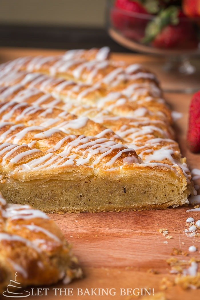 Cut puff pastry braid topped with a powdered sugar glaze on a wooden cutting board.