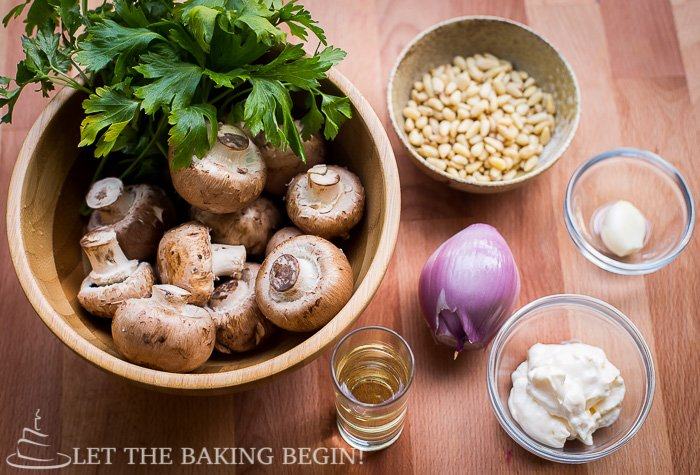 Ingredients for mushroom pate including mushrooms, pine nuts, shallot, garlic, and oil.