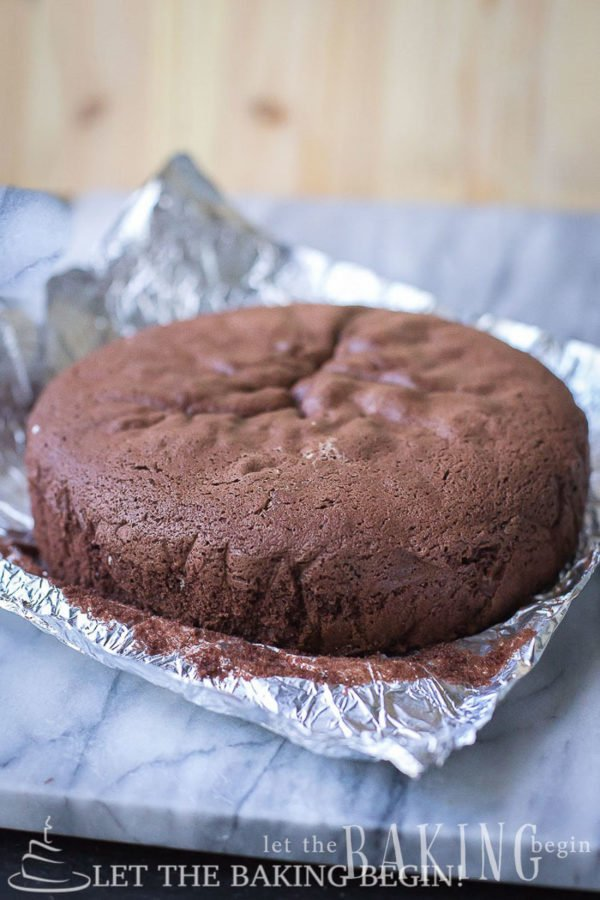 Chocolate sponge cake with foil on a platter.