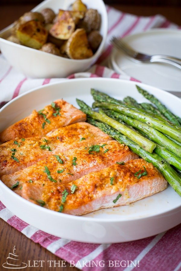 Baked salmon and asparagus on a plate next to a bowl of potatoes.