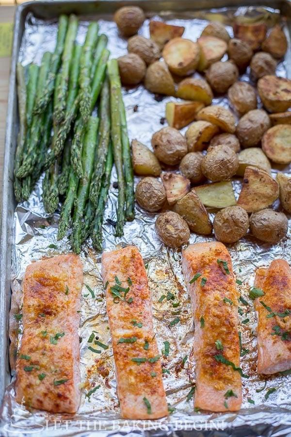 Asparagus, potatoes and seasoned salmon on a baking sheet.