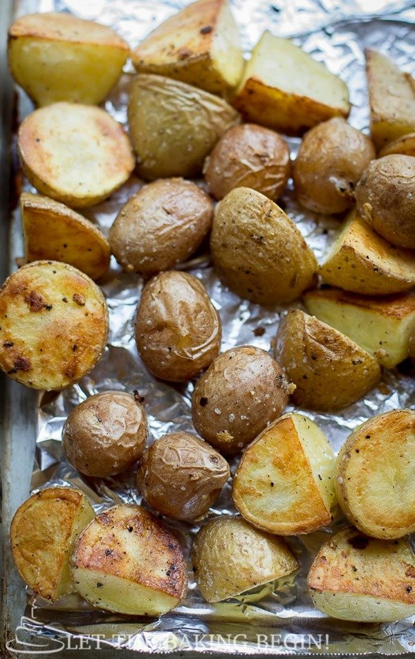 Oven baked potatoes with salt and pepper on foil lined baking sheet.