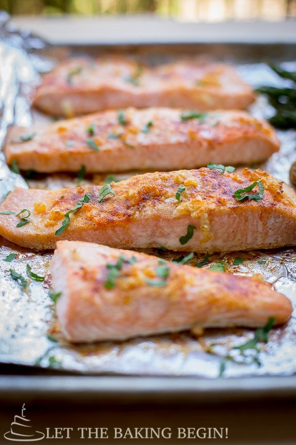 Oven baked salmon on a foil lined baking sheet topped with fresh chopped greens.