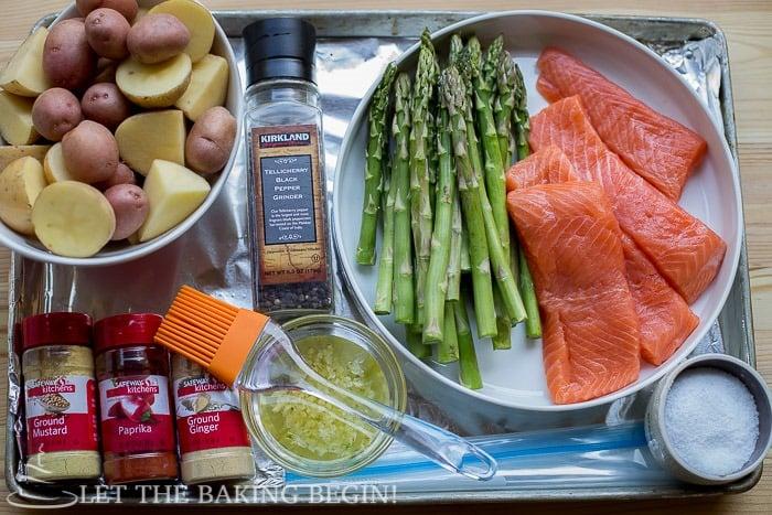Salmon, asparagus, potatoes and seasonings on a baking sheet.
