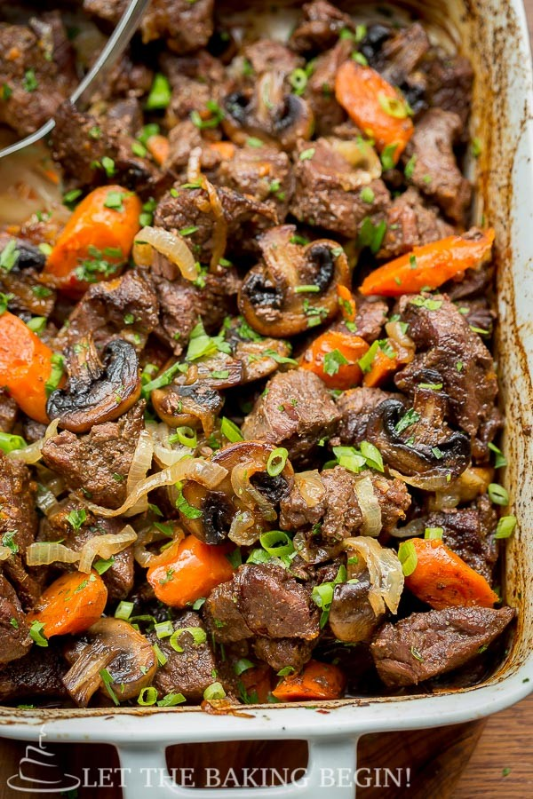 Beef Roast recipe with mushrooms, onions and carrots in a baking dish, top view.