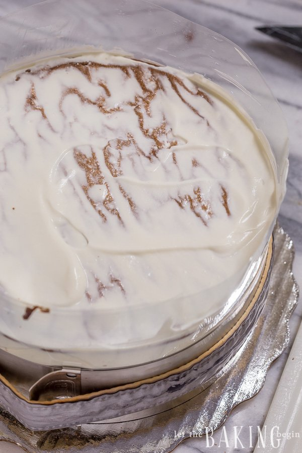 Chocolate cake covered in cream cheese frosting in a baking sheet.