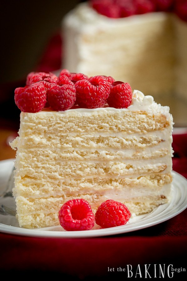 A slice of cake with cream cheese frosting in between each layer, and raspberries on top of the cake.
