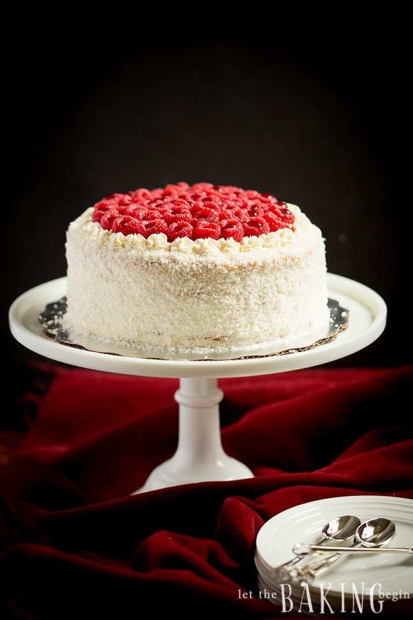 Milk cake iced and topped with raspberries. The cake is on a white stand with a red velvet tablecloth and plates and spoons in the foreground.