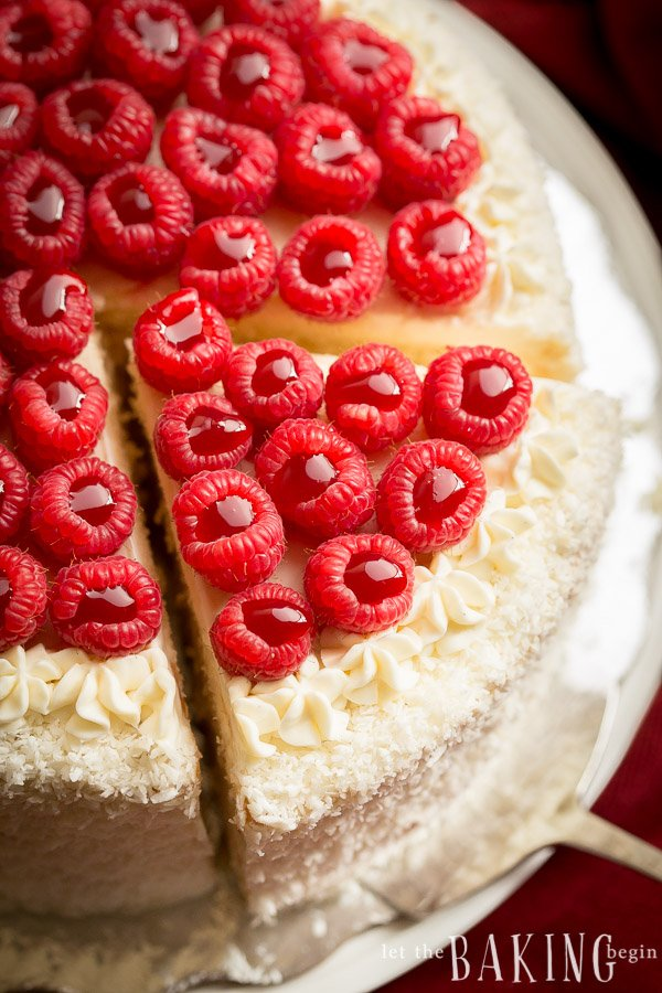 Tres leches cake topped with raspberries being sliced and served.