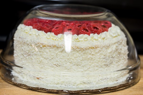 Tres leches cake with raspberries on top covered in a glass dome as it soaks overnight.