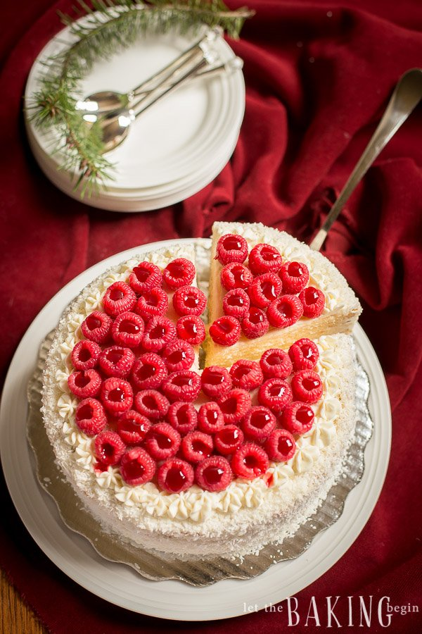 A slice of tres leches cake topped with raspberries being served. A stack of plates with spoons and a sprig of rosemary in background.