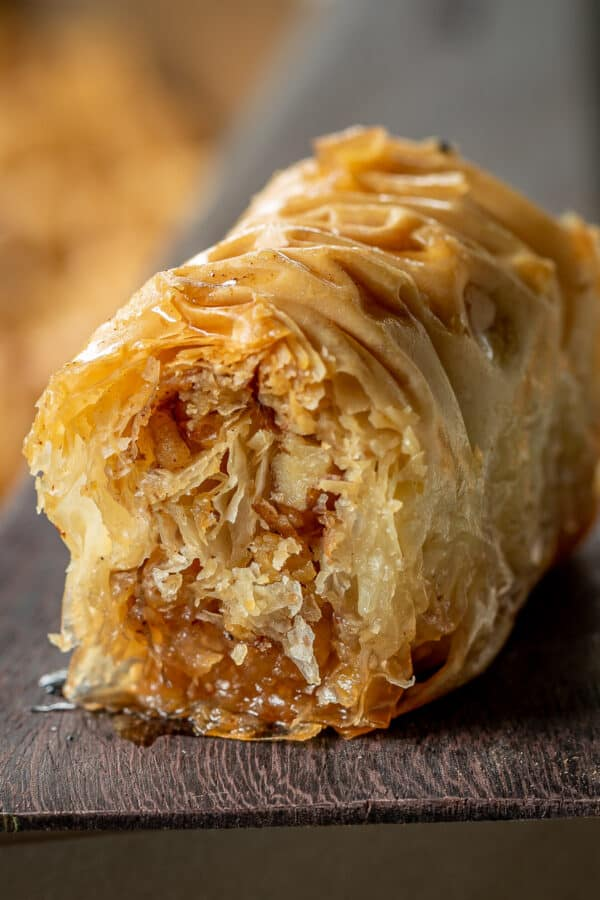 A baklava piece sitting on a spatula displaying the inside of the rolled baklava.
