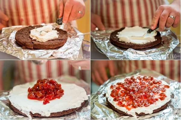 One chocolate layer is spread with cream with a scoop of cherry filling on top.
