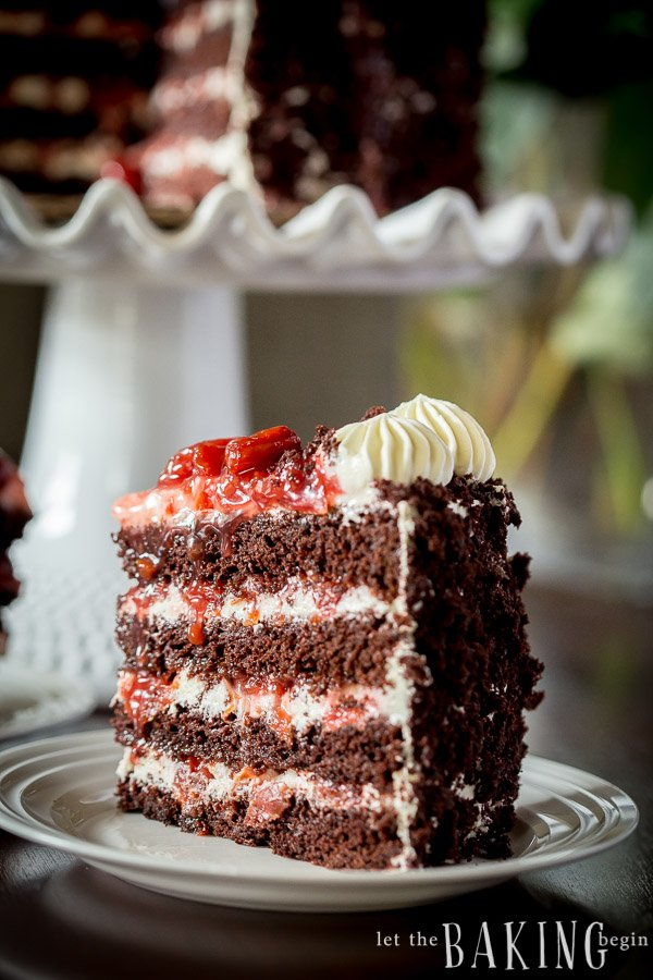 A slice of Black Forest Cake on a white platter. A whole Black Forest Cake is in the background.