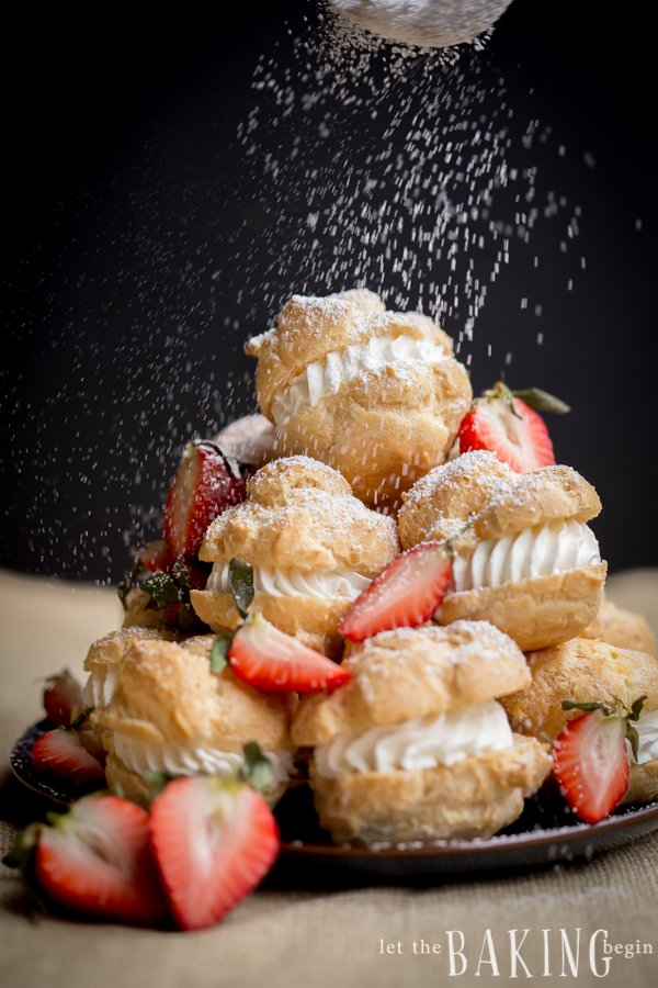 Cream puffs topped with strawberries and powdered sugar on a decorative black plate.