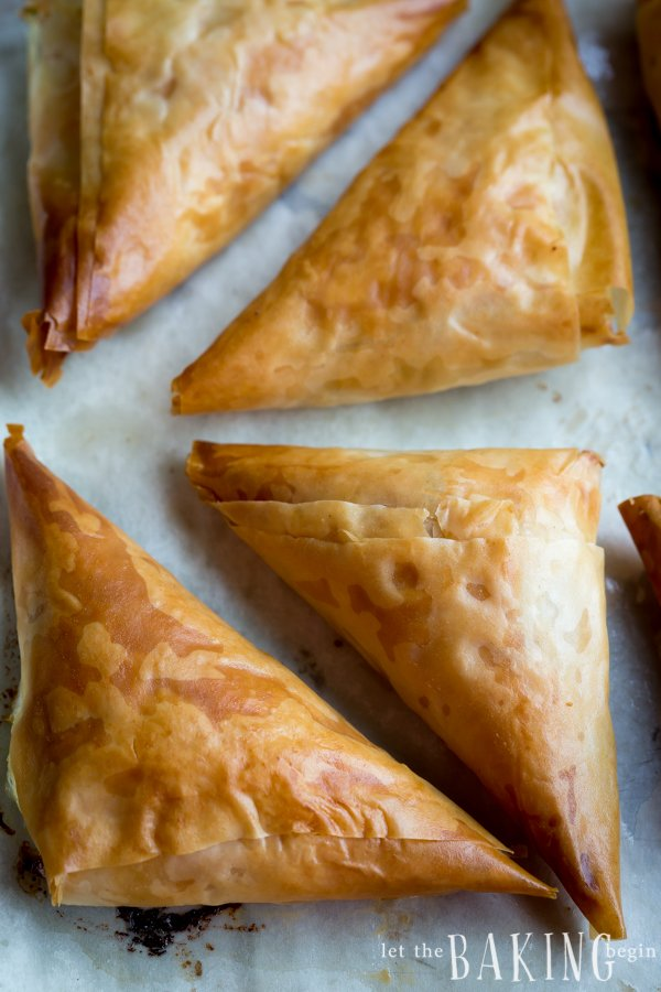 Phyllo dough triangles filled with a Feta cheese filling on a baking sheet.