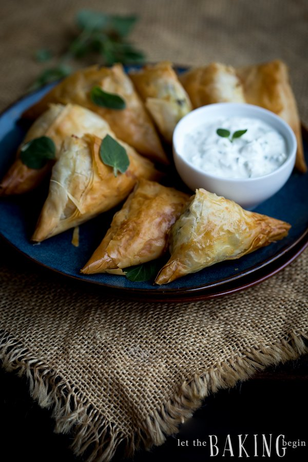 Crispy spanakopita triangles on a with a cream dip.
